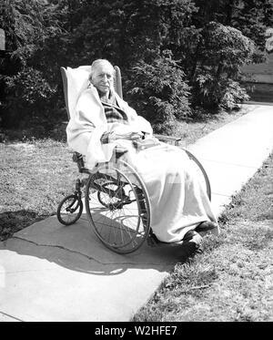 Elderly man sitting in a wheel chair ca. 1936 - Stock Image