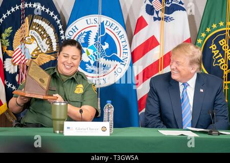 U.S President Donald Trump is presented with a gift from CBP Agent Gloria Chavez, left, during a border security roundtable at the Border Patrol Calexico Station April 5, 2019 in Calexico, California. Trump visited the section of wall at Calexico that was part of a replacement project started under President Obama. - Stock Image