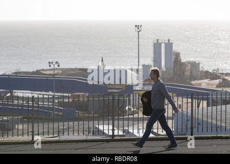 A Kent man walks along West Cliff Promenade that overlooks the Port of Ramsgate, a closed but once busy ferry terminal, on 8th January 2019, in Ramsgate, Kent, England. The Port of Ramsgate has been identified as a 'Brexit Port' by the government of Prime Minister Theresa May, currently negotiating the UK's exit from the EU. Britain's Department of Transport has awarded to an unproven shipping company, Seaborne Freight, to provide run roll-on roll-off ferry services to the road haulage industry between Ostend and the Kent port - in the event of more likely No Deal Brexit. In the EU referendum  - Stock Image