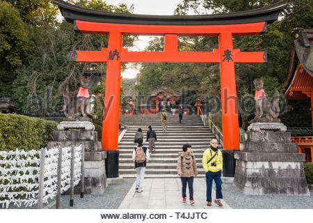 Sculptures of foxes regarded as messengers on each side of a traditional Japanese Torii gate on the grounds of the Fushimi Inari Taisha Shinto shrine, - Stock Image