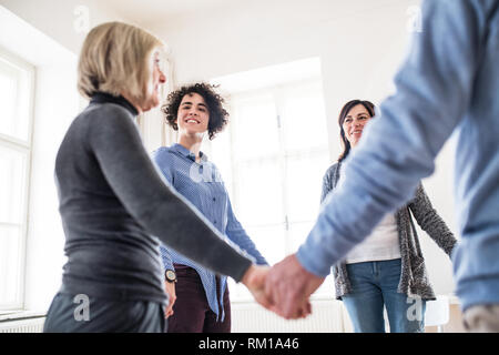 Group of people standing in a circle and holding hands during therapy. - Stock Image