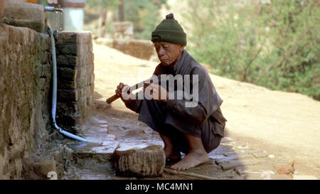 A man from Burma's indigenous, ethnic Wa tribe sharpening his knife in his village in Shan State. - Stock Image