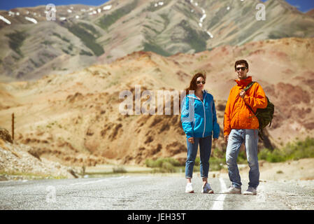 Couple backpackers on mountain road - Stock Image