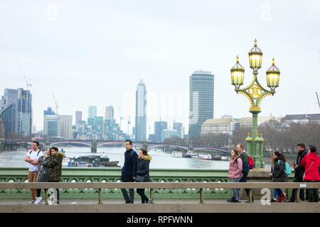People walking  over Westminster Bridge with ornate triple headed cast iron  lamp post with lights lit over the river Thames England London - Stock Image