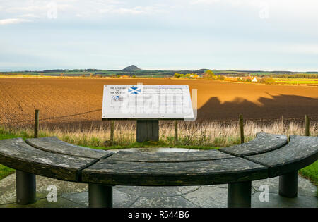 Athelstaneford, East Lothian, Scotland, United Kingdom, 29th November 2018. View across agricultural fields to Berwick Law at the birthplace of St Andrew's Cross, the saltire flag, with an information board and bench. On the eve of St Andrew's Day at the National Flag Heritage Centre. Legend says that on the eve of a battle between Picts and Angles from Northumbria in 832AD Saint Andrew had a vision of victory and when the Picts saw a white cross formed by clouds in a blue sky they attributed their victory to his blessing, adopting the cross as a flag - Stock Image