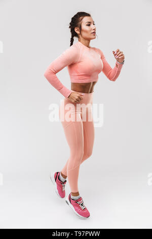 Picture of a beautiful young amazing strong sports fitness woman posing isolated over white wall background make exercises. - Stock Image