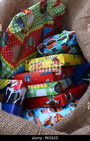 Portrait of a burlap sack full of gifts for celebrating Saint Nick - Stock Image