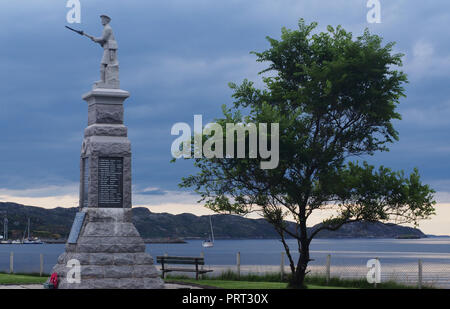 A view from Lochinver, Scotland, across the sea to the harbour with a world war one memorial with infantry man on top and tree in the foreground - Stock Image
