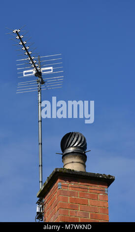 Chimney and television aerial on house, showing spinnig cowl on the top of the chimney - Stock Image