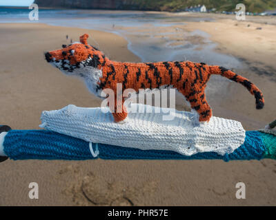 Yarn Bombing decorating public place with knitted objects here a depiction of Life of Pi story with a boy and a tiger in a boat at Saltburn Pier - Stock Image