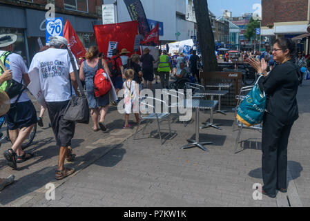 London, UK. 7th July 2018. A woman claps as Keep Our St Helier Hospital (KOSHH) campaigners against the closure of acute facilities at Epsom and St Helier Hospitals in south London celebrate the 70th Birthday of the NHS by marching from Sutton to a rally in front of St Helier Hospital.  The closures are prompted by government cuts which call for huge savings by the trust, and would leave a wi Credit: Peter Marshall/Alamy Live News - Stock Image