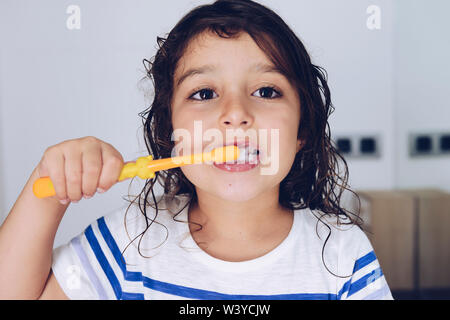 portrait of a little girl brushing her teeth in the bathroom before going to bed after taking a shower, kids hygiene concept - Stock Image