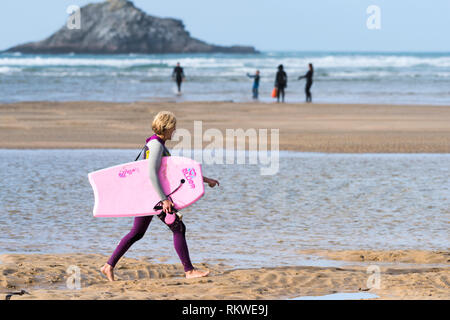 A mature female holidaymaker in a wetsuit carrying a pink body boogie board walking along the shoreline at Crantock Beach in Newquay in Cornwall. - Stock Image