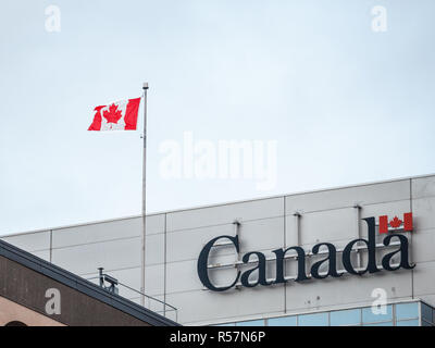 OTTAWA, CANADA - NOVEMBER 10, 2018: Canada Wordmark, the official logo of the Canadian government, on an administrative building next to a Canadian fl - Stock Image