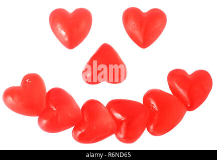 Bright red jelly heart shaped sweets in the shape of a smiling happy face isolated on white background - Stock Image