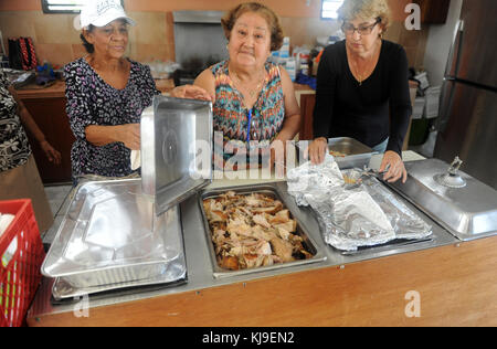 Volunteers Ana Luis Vazquez, left, Dalila Gonzalez, and Mary Rolon, right, show off a tray of roasted turkey for - Stock Image