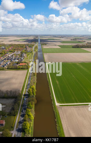 Long straight canal next to road, near Amsterdam, North Holland, The Netherlands - Stock Image