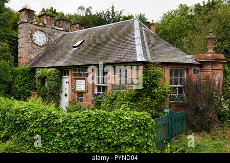 West Clock Lodge coach house in Sheriffmoor Plantation Forest at Eagle Lodge Scottish Borders Scotland UK with ivy and clock on chimney - Stock Image