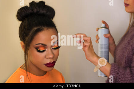 Young woman African American with perfect skin facial. Fashion luxury makeup orange-coloured shades. Long eyelashes, pouty lips. Upper bun hair. Profe - Stock Image