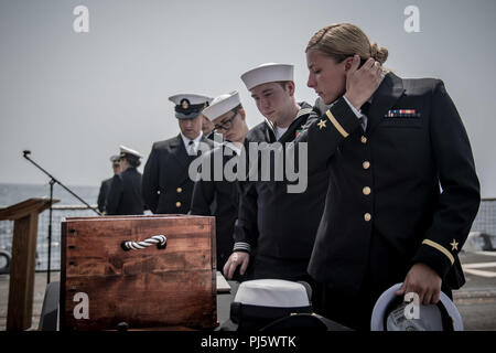 180825-N-UX013-1121 U.S. 5TH FLEET AREA OF OPERATIONS (Aug. 25, 2018) Sailors pay tribute at a shadow box display for Ensign Sarah Mitchell during a memorial ceremony at sea aboard the guided-missile destroyer USS Jason Dunham (DDG 109). Dunham is deployed to the U.S. 5th Fleet area of operations in support of naval operations to ensure maritime stability and security in the Central Region, connecting the Mediterranean and the Pacific through the western Indian Ocean and three strategic choke points. (U.S. Navy photo by Mass Communication Specialist 3rd Class Jonathan Clay/Released) - Stock Image