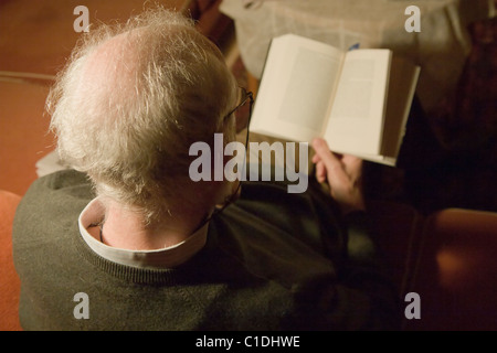 Elderly man reading a book. - Stock Image