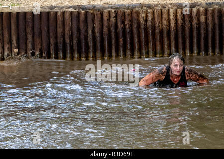 Impromptu washing by a middle aged woman during a mud run - Stock Image