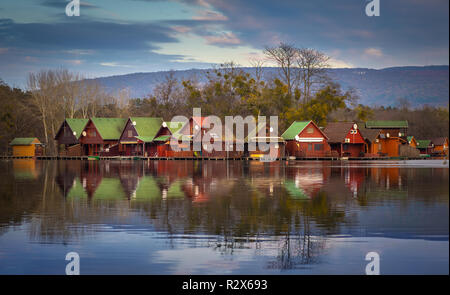 Tata, Hungary - Fishing cottages by the lake Derito on a small island at sunset with reflections and colourful sky and clouds - Stock Image