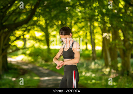 sportswoman checking her watch after jogging and exercise. - Stock Image