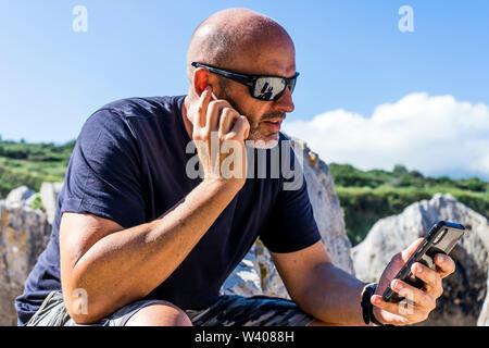 bald man on beach using headphones and mobile phone - Stock Image