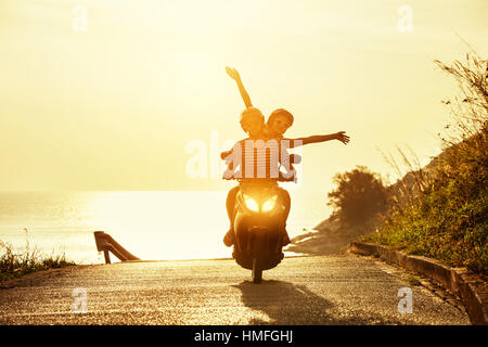 Happy couple travel motorcycle sea road - Stock Image