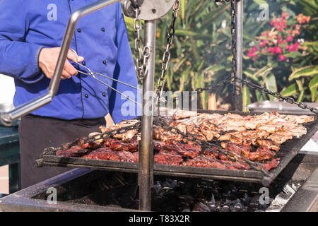 Close up of outdoor big barbecue bbq grill for restaurant or catering business concept - fresh meat and tasty food for people - man cooking outdoor wi - Stock Image