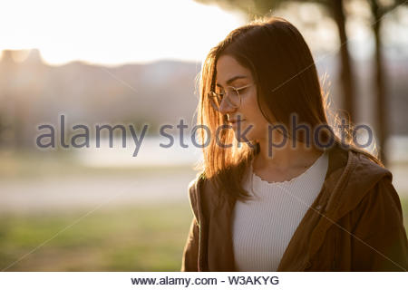 Front portrait of beautiful woman in a park during sunset with copy space - Stock Image