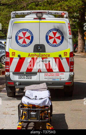 New South Wales ambulance at the beach with stretcher awaiting a patient being moved from the beach,Sydney,Australia - Stock Image