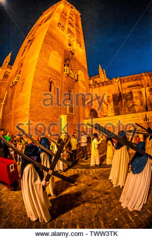 Hooded Penitents (Nazarenos) in the procession of the Brotherhood (Hermandad) San Benito carrying crosses, Holy Week (Semana Santa), Seville, Andalusi - Stock Image