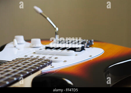 Looking over the bridge, scratchplate and vibrato arm of an electric guitar. - Stock Image