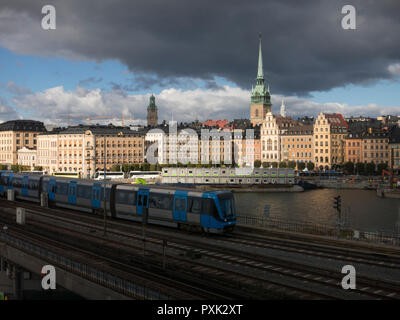 Dark clouds over Stockholm Old Town as seen from Slussen with an underground train in the foreground - Stock Image