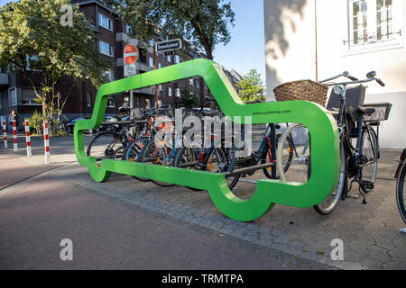 Bicycle stand in the shape of a car, this should visualize that almost 10 bicycles can park on the space of a car  Dusseldorf, Germany, Kennedydamm, - Stock Image