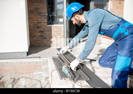 Builder in uniform measuring metal window sills for cutting on the construction site - Stock Image