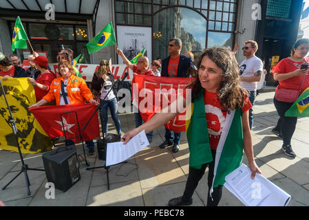 London, UK. 13th August 2018.  A woman hands out flyers as Brazilians protest outside the Brazilian embassy calling for the release of Luiz Inacio Lula da Silva, a former trade union leader who was President of Brazil from 2003-11 to enable him to stand for election again in October. Credit: Peter Marshall/Alamy Live News - Stock Image