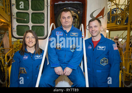 International Space Station Expedition 59 crew members Nick Hague of NASA (right), Christina Koch of NASA (left) and Alexey Ovchinin of Roscosmos (center) pose for pictures in front of the Soyuz MS-12 spacecraft during final inspection at the Baikonur Cosmodrome March 10, 2019 in Baikonur, Kazakhstan. Expedition 59 crew: Christina Koch of NASA, Alexey Ovchinin of Roscosmos, and Nick Hague of NASA will launch March 14th onboard the Soyuz MS-12 spacecraft for a six-and-a-half month mission on the International Space Station. - Stock Image