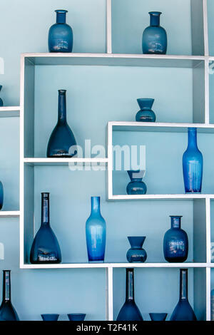 Retro style blue glass bottles in a beautiful arrangement on shelves attached to a light blue wall. - Stock Image