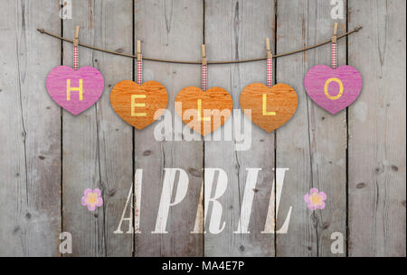 Hello April written on hanging pink and orange hearts and weathered wooden background, with flowers - Stock Image