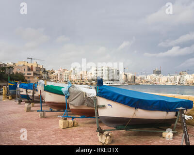 Row of colourful fishing boats on land in Exiles Bay, Saint Julians, Malta - Stock Image