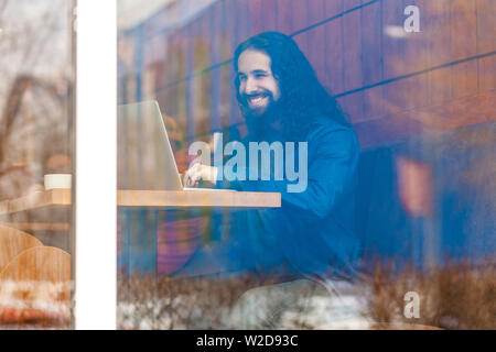 Portrait through the window of handsome young adult man freelancer in casual style sitting in cafe, chating with his friend in laptop, bussinessman in - Stock Image