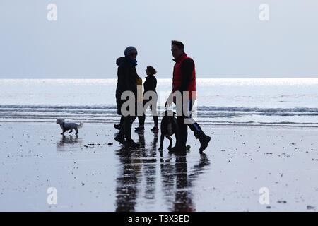 Hastings, East Sussex, UK. 12 Apr, 2019. UK Weather: Bright with sunny intervals in the seaside town of Hastings in East Sussex. A family with dogs enjoying the seaside. © Paul Lawrenson 2019, Photo Credit: Paul Lawrenson/Alamy Live News - Stock Image
