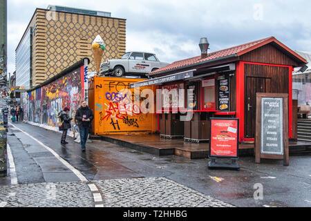 Berlin,Friedrichshain. Berlin Wall East Side Gallery. Wall segment, Currywurst kiosk & old Trabant car - Stock Image