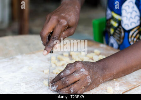 Close-up on female hands cutting a paste of flour On a board with natural light - Stock Image