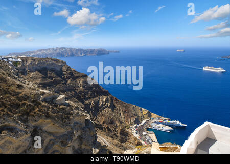 View from the hills near Oia of the cruise and boat port and ships at sea inside the caldera on the island of Santorini, Greece. - Stock Image