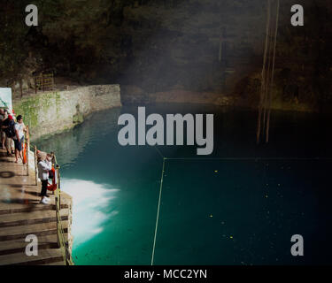 Tourists photograph a cenote (sink hole) where humans were sacrificed near the ancient  Mayan site of Chichén Itzá, Yucatán State, Mexico. - Stock Image