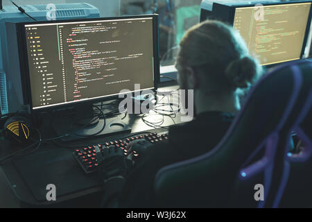 Rear view of concentrated software engineer sitting at table and composing app script while working in programming company - Stock Image